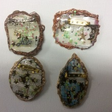 Back of hand made bezel brooches and necklaces.